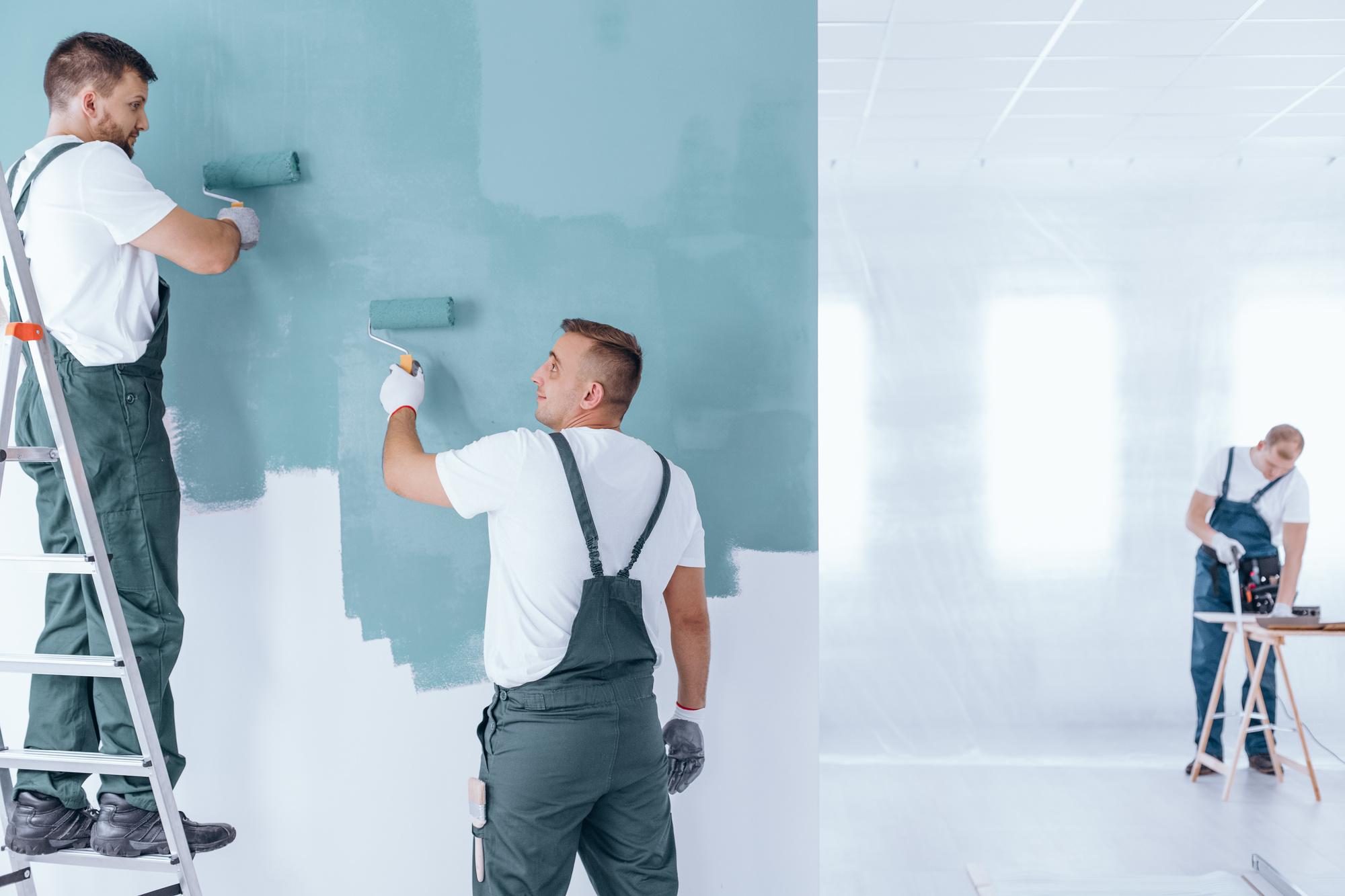 Men painting empty home interior